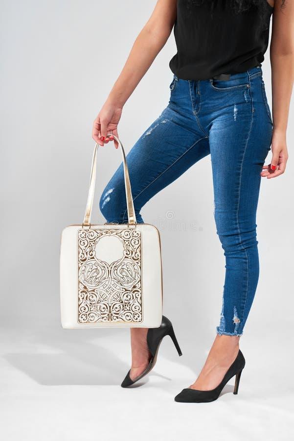 Fashionable white bag on the woman s legs background stock photos