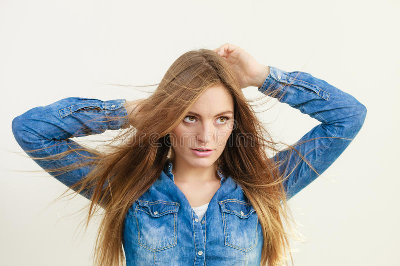Fashionable woman with blowing hair. Female fashion and haircare. Fashionable young attractive woman wearing denim jeans shirt. Girl with brown long hair waving stock photos