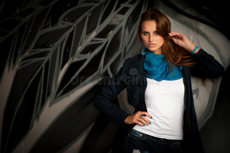 Fashionable woman with blured graffitti in background. Fashionable woman with blue scarf standing infront of blured graffitti in background royalty free stock photos