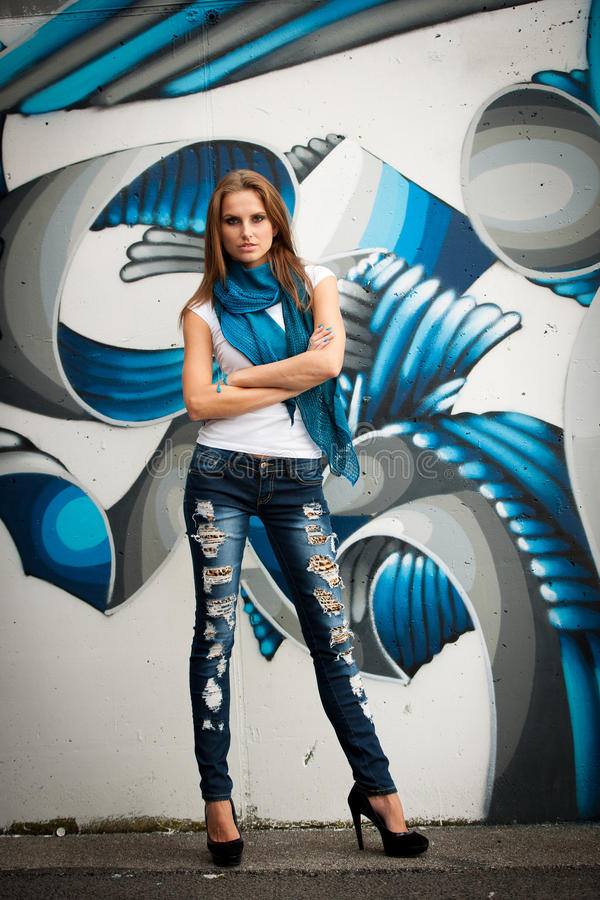 Fashionable woman with blured graffitti in background. Modern dressed stock image