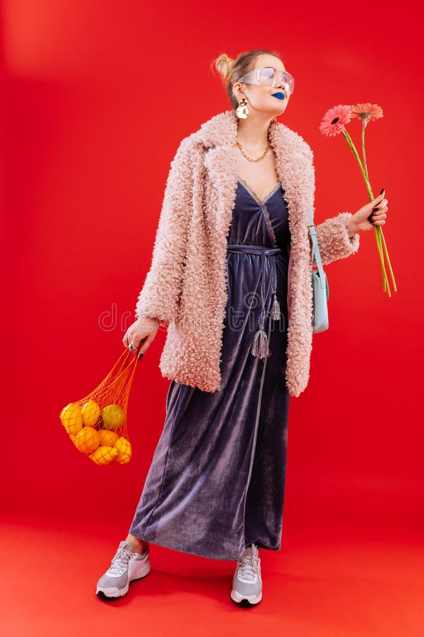 Fashionable woman coming home with bag of fruits and flowers. Fruits and flowers. Fashionable blonde-haired woman coming home with bag of fruits and flowers royalty free stock images