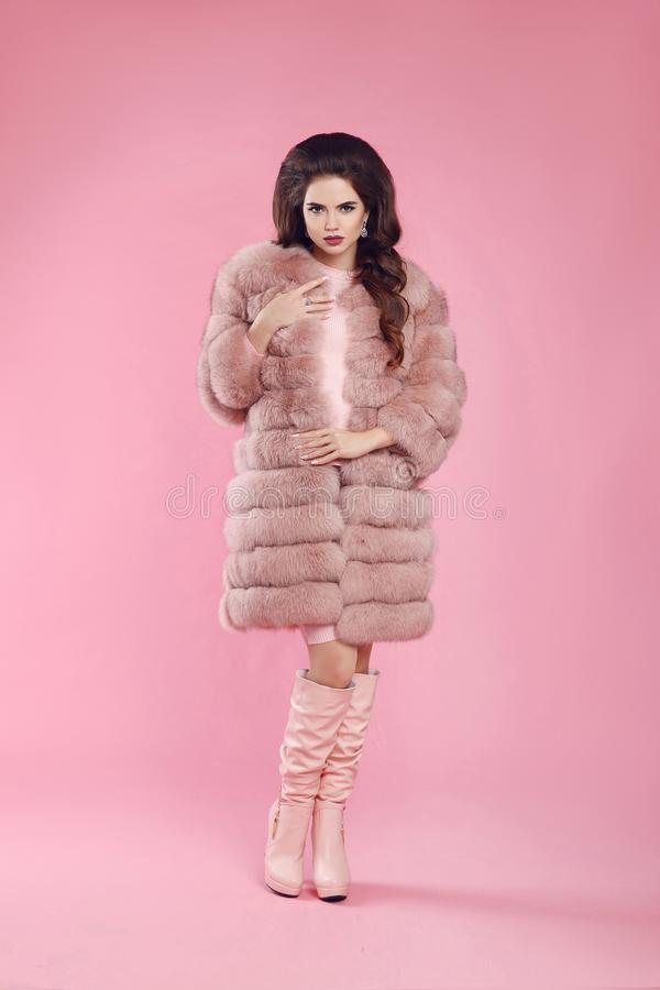 Fashionable woman in fur coat and leather high boots, lady portrait over pink studio background. Beautiful brunette model in stock photography