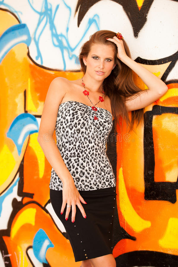 Fashionable woman with graffitti in background. Fashionable woman with blured graffitti in background stock photography