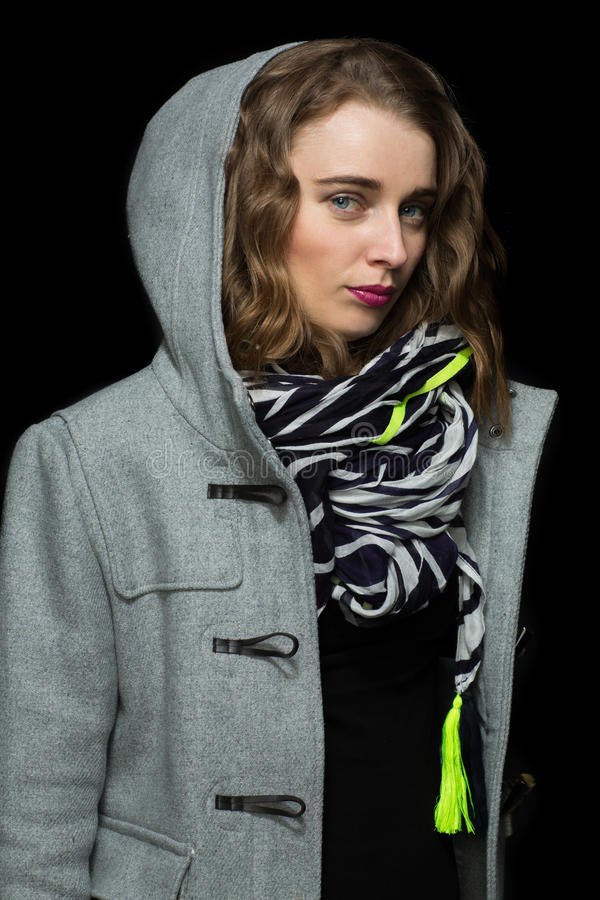 Fashionable woman in a grey hooded coat. Fashionable beautiful young woman in a grey hooded coat and matching scarf standing looking sideways at the camera with royalty free stock photography