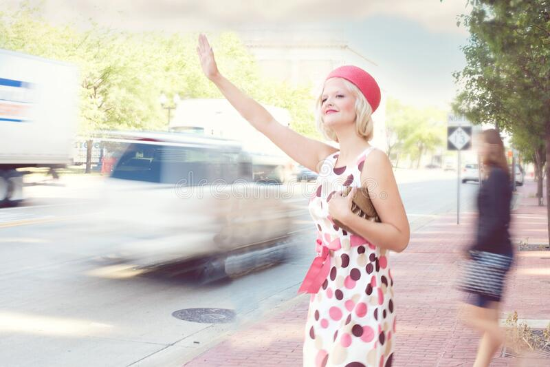 Fashionable woman hailing taxi cab stock photography