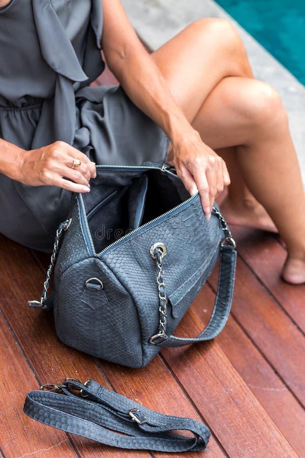 Fashionable woman holding luxury stylish snakeskin python bag. Elegant outfit. Close up of purse in hands of stylish. Lady. Model posing stock photography