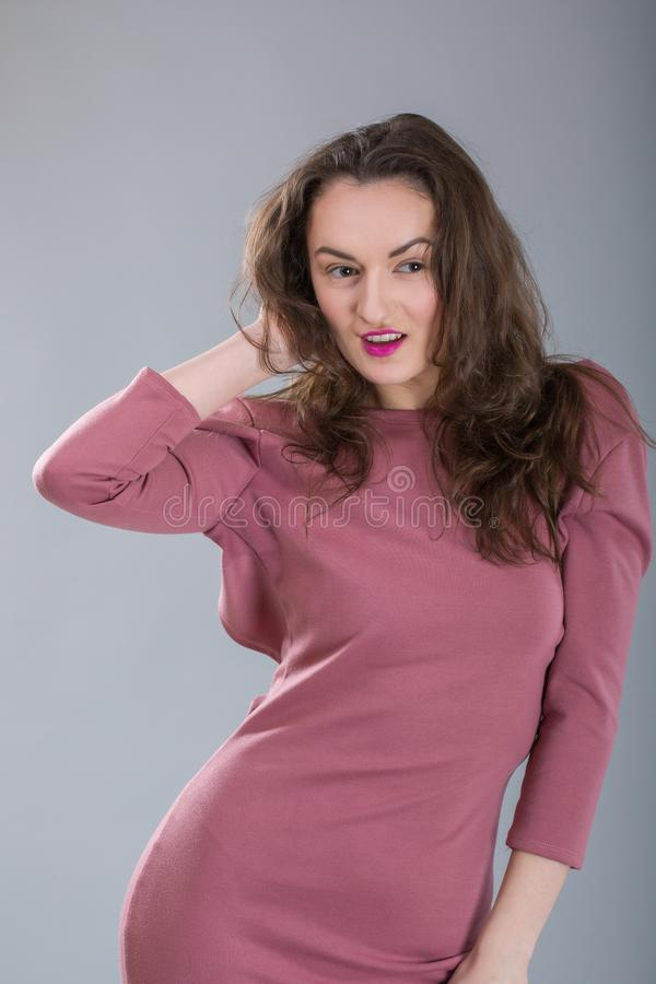 Fashionable woman with long brunette hair and red pretty smiling happy face in stylish pink dress in studio on grey background stock photos