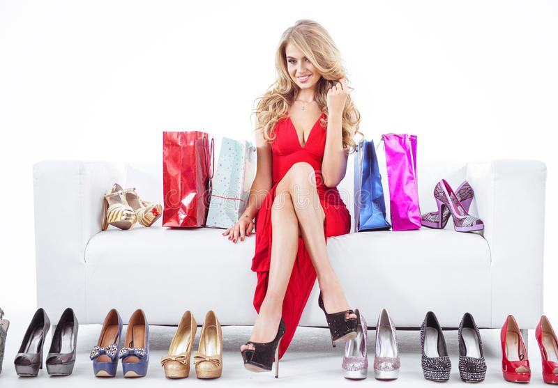 Fashionable woman with lots of shoes royalty free stock photo