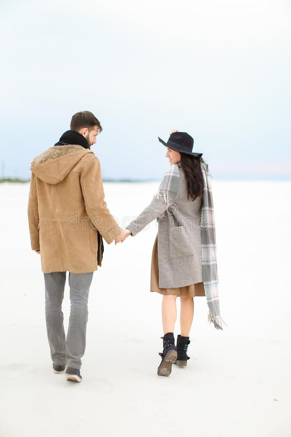 Fashionable woman and man walking on snow and holding hands, wearing coat, grey scarf and hat. Fashionable women and men walking on snow and holding hands stock photography
