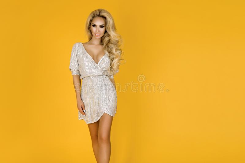 Fashionable woman in trendy sequins mini dress, shoes and accessories. Fashion spring summer photo. Happy young girl on a yellow. Fashionable woman model in royalty free stock images