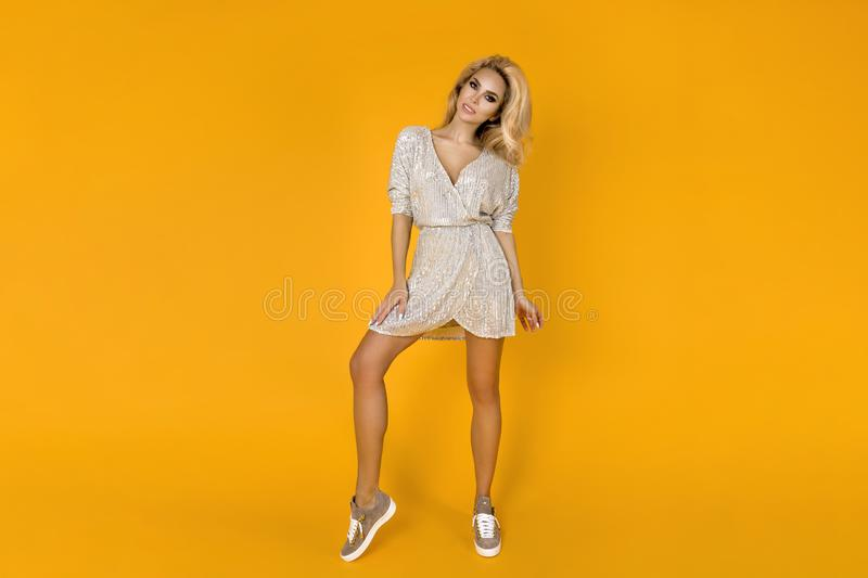 Fashionable woman in trendy sequins mini dress, shoes and accessories. Fashion spring summer photo. Happy young girl on a yellow. Fashionable woman model in royalty free stock image