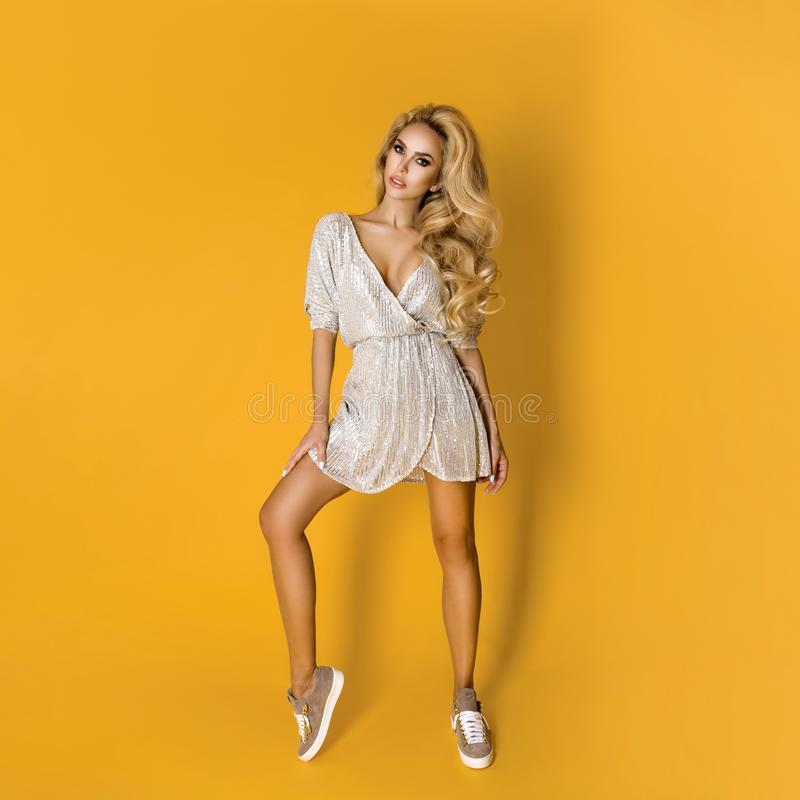 Fashionable woman in trendy sequins mini dress, shoes and accessories. Fashion spring summer photo. Happy young girl on a yellow. Fashionable woman model in stock images
