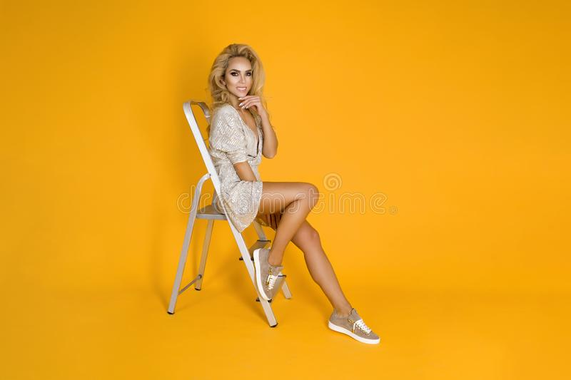 Fashionable woman in trendy sequins mini dress, shoes and accessories. Fashion spring summer photo. Happy young girl on a yellow. Fashionable woman model in royalty free stock photos