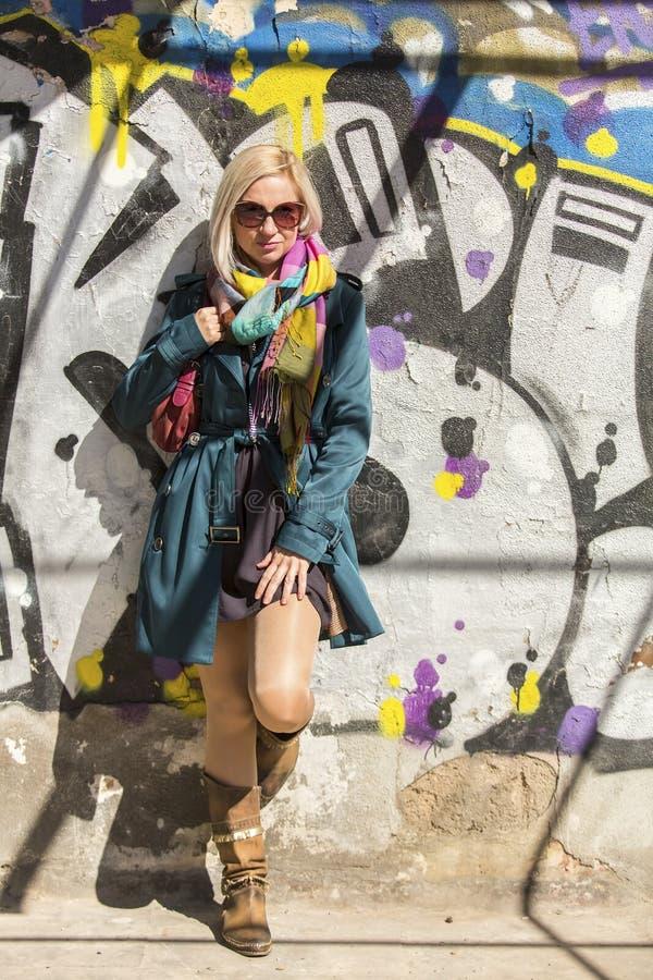 Fashionable woman near the urban street wall. Young fashionable woman near the urban street wall royalty free stock image