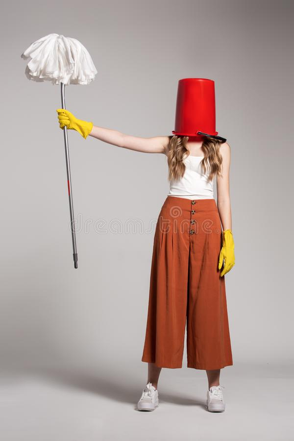 Fashionable woman with a red bucket on her head holding a mop. royalty free stock photo