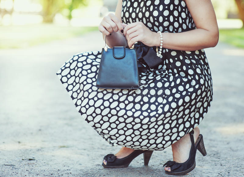 Fashionable woman with small bag in her hands and dress sitting stock image