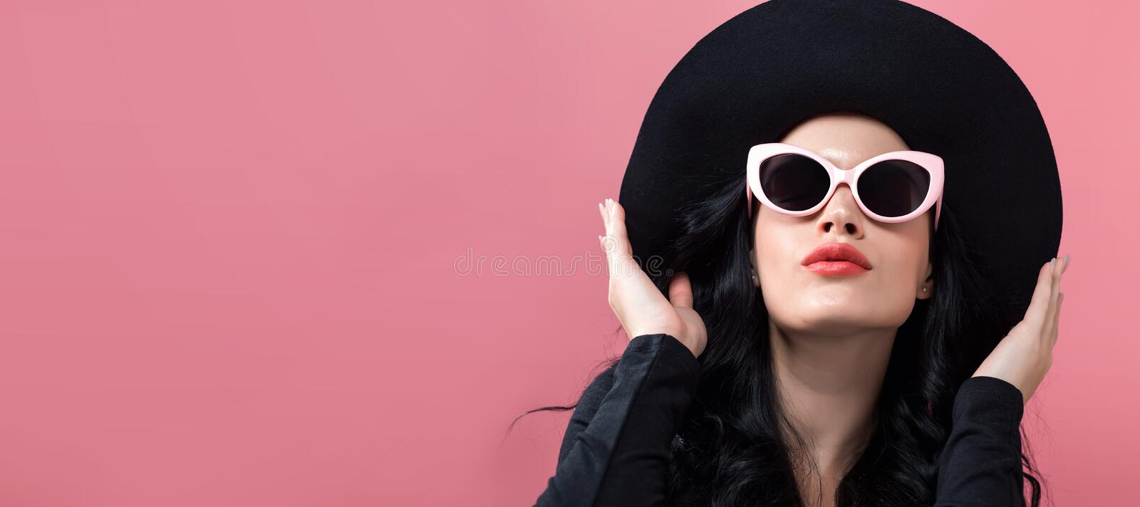Fashionable woman in sunglasses. On a pink background stock photography