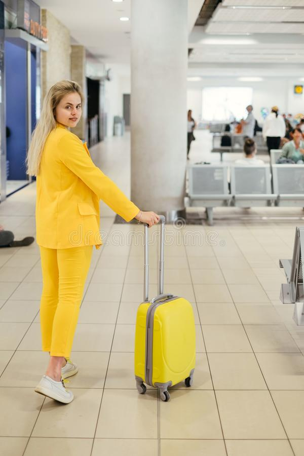 Fashionable woman traveler going to the gates of airport. Happy fashionable woman traveler going to the gates with yellow suitcase. Business person in airport royalty free stock photography