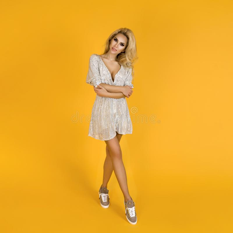Fashionable woman in trendy sequins mini dress, shoes and accessories. Fashion spring summer photo. Happy young girl on a yellow. Fashionable woman model in stock image
