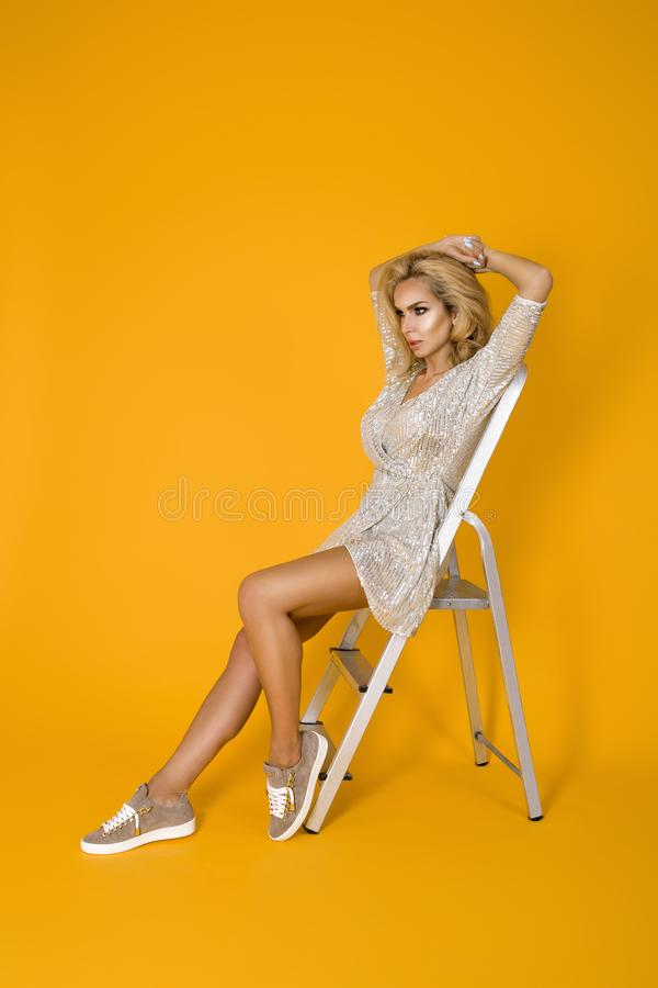 Fashionable woman in trendy sequins mini dress, shoes and accessories. Fashion spring summer photo. Happy young girl on a yellow. Fashionable woman model in stock photo