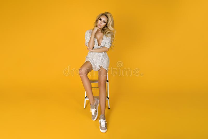 Fashionable woman in trendy sequins mini dress, shoes and accessories. Fashion spring summer photo. Happy young girl on a yellow. Fashionable woman model in royalty free stock photography
