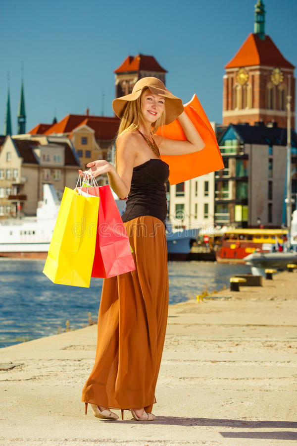 Fashionable woman walking with shopping bags. Spending money on sales, buying things concept. Fashionable woman walking with shopping bags through the town royalty free stock photos