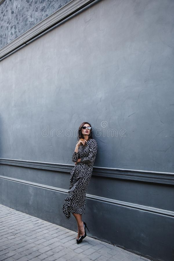 Fashionable woman wearing a black polka dot designer dress. ideal summer outfit. european fashion blogger streetstyle. stock image