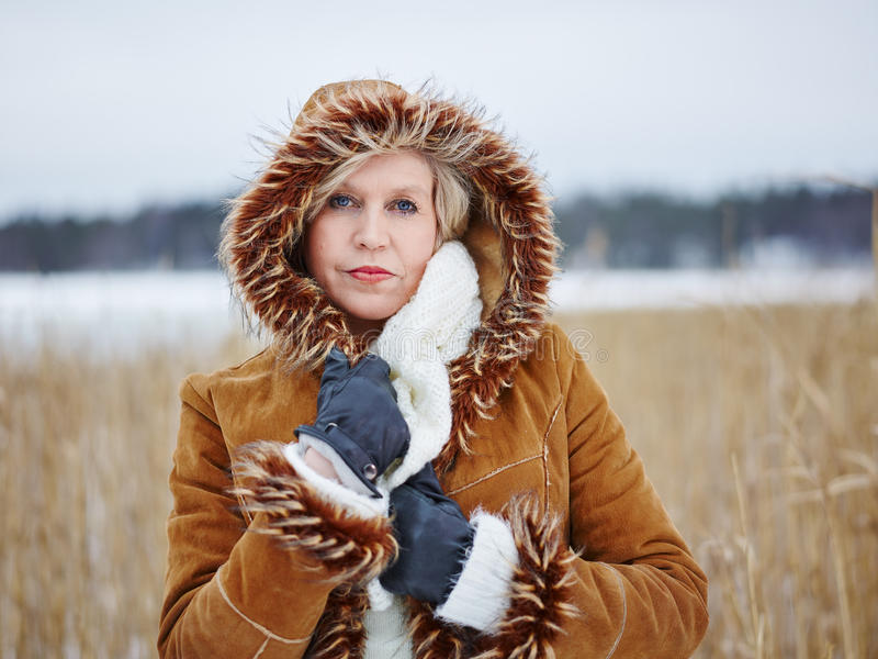 Fashionable woman and winter clothes - rural scene. Close up, fashionable mature adult woman wearing winter clothes, frozen sea and reeds on background royalty free stock photos