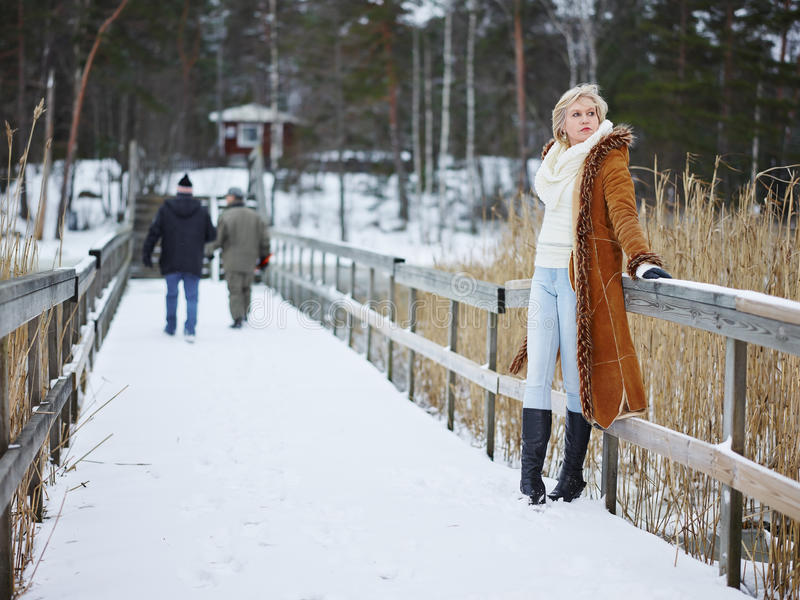 Fashionable woman and winter clothes - rural scene. Fashionable mature adult woman wearing winter clothes and she standing next to the fence - rural scene stock photos