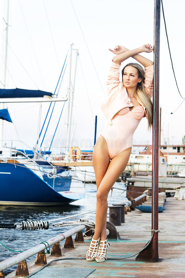 Fashionable woman on yacht's moorage. Fashionable woman relaxing on yacht's moorage stock images