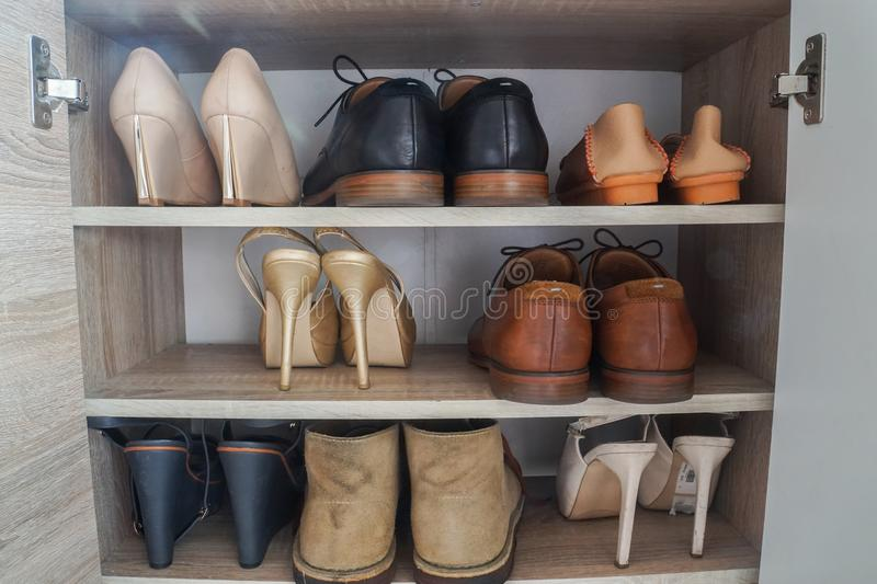 Fashionable women high heels and leather men shoes in wooden cabinet for going to work stock photography