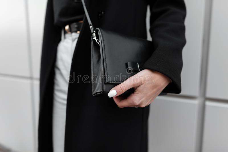 Fashionable women`s black leather stylish bag. Modern young girl in stylish clothes. Fashion spring-autumn. New collection. Close-up stock image