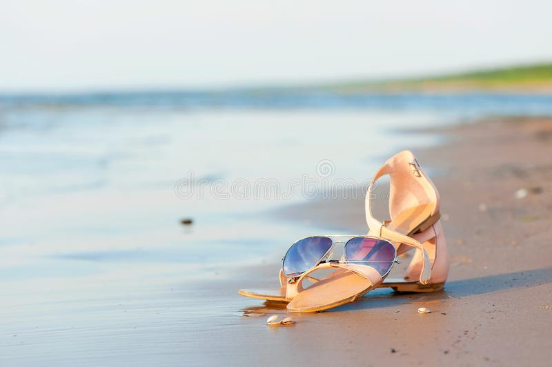 Fashionable women sandals and sunglasses on summer sandy wet coastline stock image