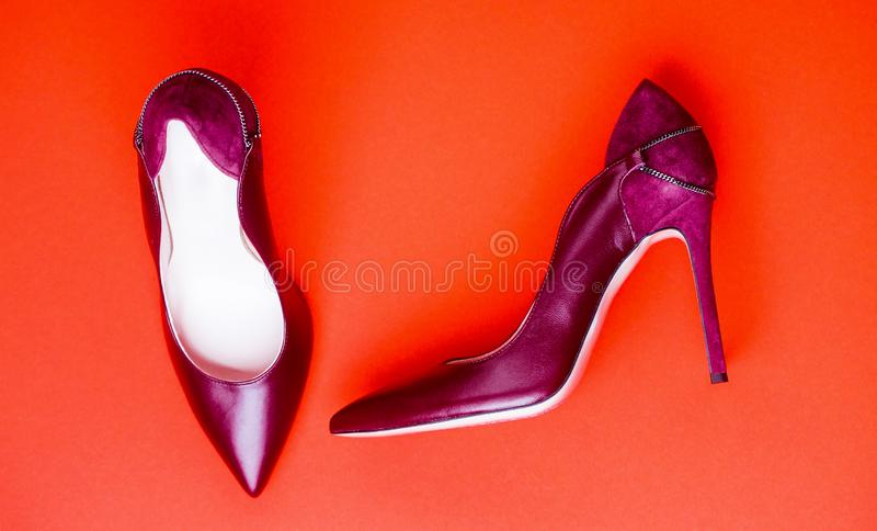 Fashionable women shoes isolated on red background. Stylish classic women leather shoe. Maroon high heel women shoes on royalty free stock image