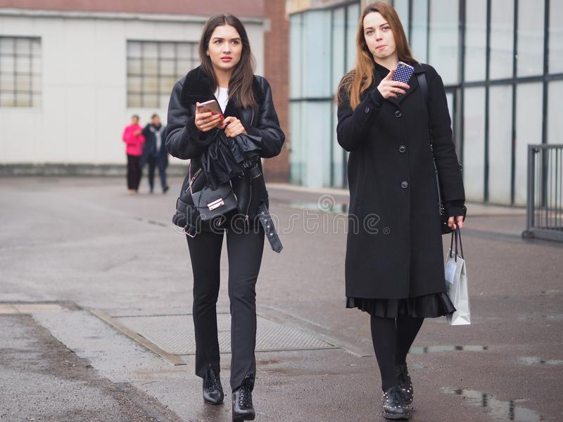 MILAN - FEBRUARY 22, 2018: Fashionable women walking in the street before LES COPINS fashion show. Fashionable women walking in the street before LES COPINS royalty free stock photo