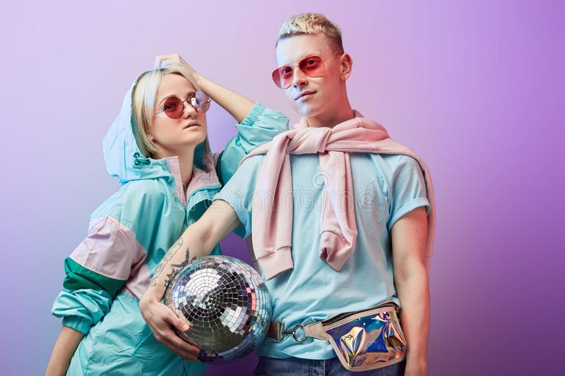 Young fashionable couple of dancers posing with disco ball on violet background royalty free stock images