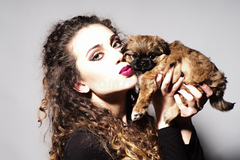 Fashionable young beautiful girl and puppy. Portrait of fashionable young beautiful girl with curly hair and bright make up holding and kissing cute little brown stock photo
