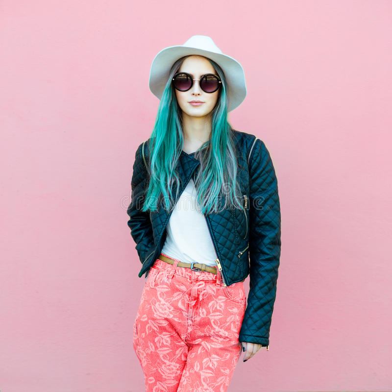 Fashionable young blogger woman with blue hair wearing casual style outfit with black jacket, white hat, pink jeans and sunglasses stock photo