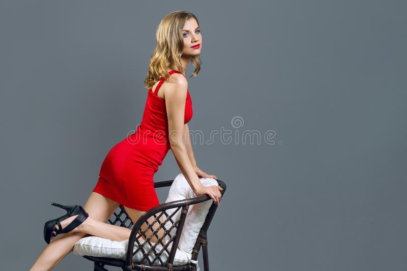 Fashionable young blonde girl in red dress stock images