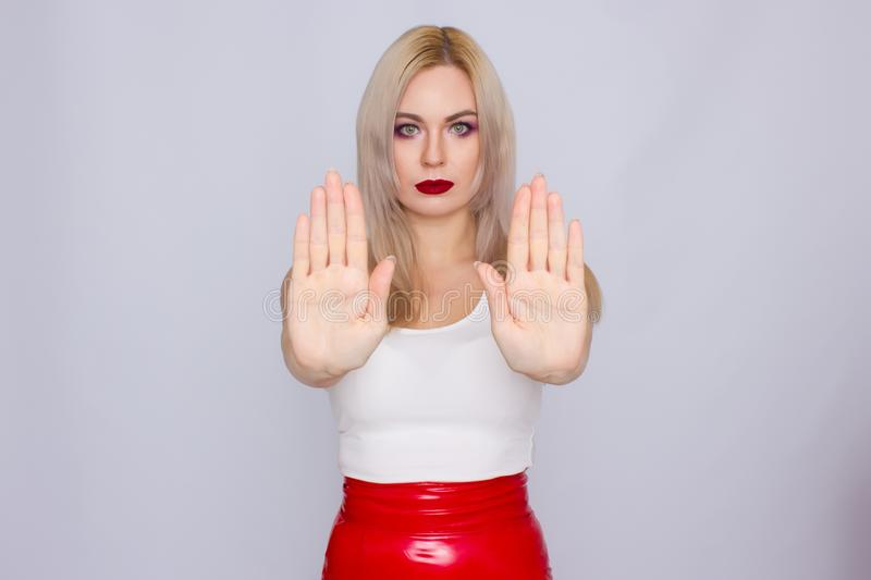 Blonde woman in red leather skirt and white shirt. Fashionable young blonde woman posing wearing red leather skirt and white shirt , looking to camera stock photos