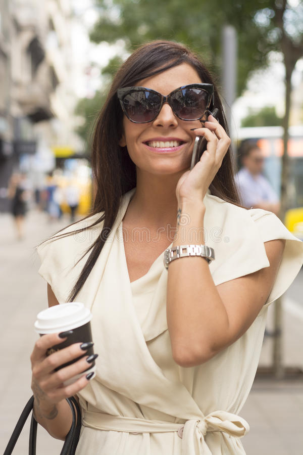 Fashionable young brunette laughs into phone stock photo