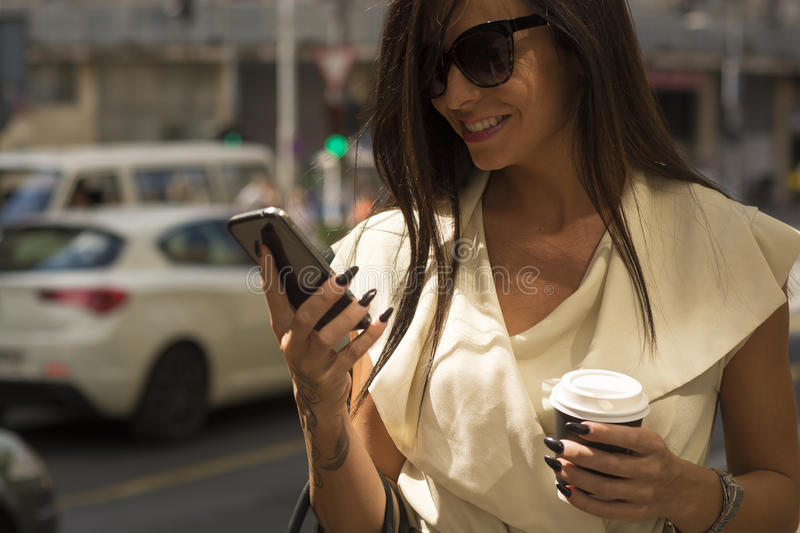 Fashionable young brunette laughs into phone stock photography