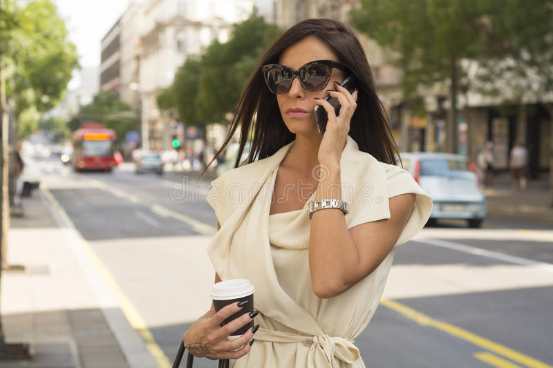 Fashionable young brunette laughs into phone royalty free stock photo