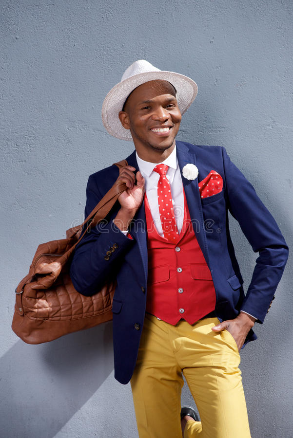Fashionable young businessman smiling with bag royalty free stock photo