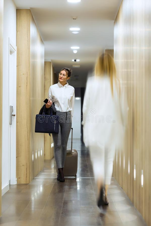 Fashionable young businesswoman walking with suitcase looking for her room in the corridor of the hotel royalty free stock images