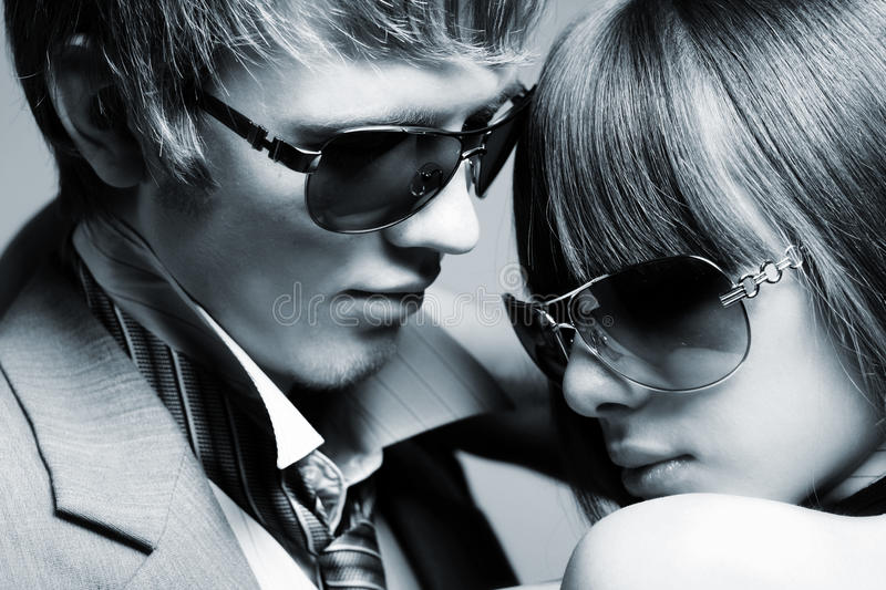 Fashionable young couple wearing sunglasses royalty free stock photography