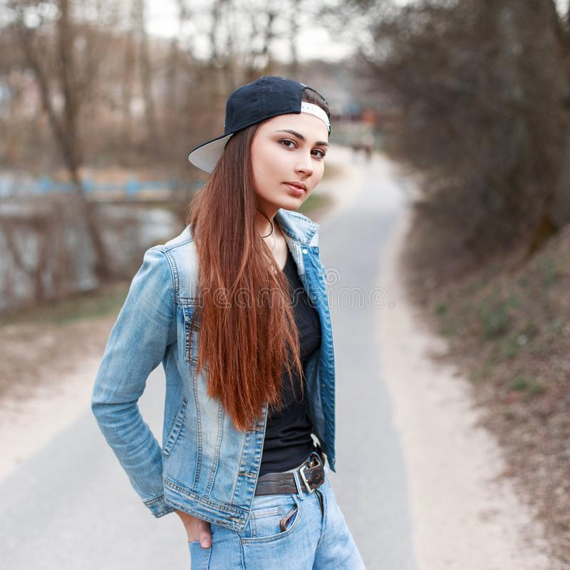 Fashionable young girl in a black cap and jeans jacket standing royalty free stock images