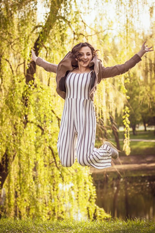 Fashionable young girl jumping happily on the background of the park stock photo