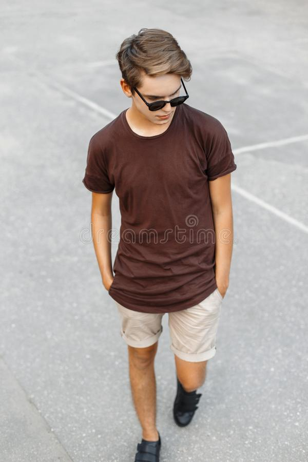 Fashionable young handsome boy in T-shirt and shorts walking stock image