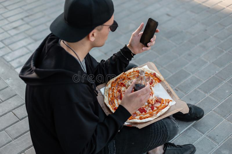 Fashionable young hipster man in stylish black clothes with a pizza with a glass bottle sits on the sidewalk. And working in the phone. Modern American guy is royalty free stock photos